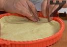 Разбиваме съставките за тестото с миксер. Разточваме кръгла кора с големината на формата за киш или тавата, в която ще печем. Поставяме тестото и изтегляме краищата, така че да покрият стените на силиконовата форма.