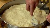 Намазняваме дъното на кръгла тава. Пресипваме свареното тесто и го разстиламе в тавата.