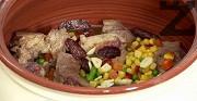 Прехвърляме месото и зеленчуците, добавяме едро нарязания чесън и останалия суджук. Похлупваме и поставяме във фурната. До 30-тата минута печем ястието на 200 градуса, след което намаляваме до 160-170 градуса и печем още 1 час.
