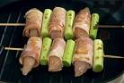 Завиваме натопено в сос пилешко късче в лентичка от бекона, като се стараем да пристегнем добре. Така навиваме цялото месо. Нарязваме праза с дължината на месните рулца. Набождаме на всяко шишче три рулца, а между тях поставяме по парче праз лук. Печем на умерено затоплена скара по 7-8 мин. от всяк