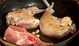 Нарязваме заека на порции. В сгорещения зехтин запържваме за кратко целите скилидки чесън. Поставяме парчетата месо и запържваме за 5-6 мин. до порозовяване.