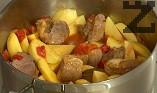 Нарязваме картофите на едри парчета, прибавяме към омекналото месо. Поливаме с 200 мл гореща вода. Похлупваме и варим за още 10 мин., докато омекнат картофите.