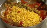 Добавяме царевицата и маслините, поръсваме с червен пипер и риган. Задушаваме за още 1-2 мин.