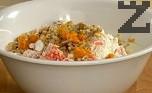 В друга купа счупваме яйцата, смесваме ги със захарта. Разбиваме с миксер до получаване на пухкава смес. Постепенно прибавяме олиото, като бъркаме непрекъснато. Добавяме сместа с ябълки и моркови. Поръсваме с едро смлените орехови ядки и портокаловата кора.