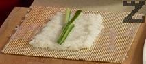 Накисваме оризовата хартия в съд с вода. В единия край на увита с фолио дървена рогозка за суши поставяме ориза, като го оформяме на правоъгълник с ширина 2 пръста.