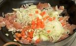 Нарязваме чесъна и моркова на кубчета, а лука - на полумесеци. Прибавяме ги към месото.