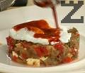 Поливаме със запържен в масло червен пипер. Декорираме с парченца сушен домат.