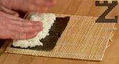 Предварително сваряваме ориза. Върху рогозка за суши, покрита с фолио, поставяме листа Нори с гланцовата страна надолу. Подреждаме отгоре охладения ориз.