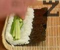 Нарязваме краставицата на тънки пръчици, нареждаме върху ориза. С помощта на рогозката завиваме на руло, като намазваме единия край на кората с вода.