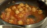 Добавяме меда и обелените и нарязани на малки парченца домати, варим на слаб огън за още 5-6 мин. Прехвърляме върху качамака, оформяме две кладенчета.