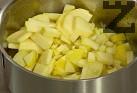 Без да ги обелваме, режем ябълките на кубчета и ги задушаваме за няколко минути в загрятото масло. Поръсваме със захар.