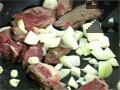 Нарязваме на ситно кромид лук и 2 скилидки чесън, изсипваме ги при месото и пържим до златисто.