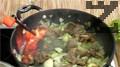 Фламбираме с бренди, добавяме половината печена чушка и консервирани домати и готвим ястието до готовност.