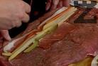 В едната част по дължина редим нарязаните на жулиени моркови и краставички, аспержите и филийките шунка.