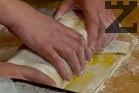 Изваждаме рулото от тавата, поставяме на дъното шайбите дюли. Поръсваме бутер тестото с малко брашно, намазваме го с жълтък. Завиваме изпеченото руло, като предварително сме отстранили конеца.