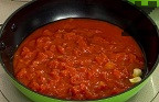 Приготвяме соса. Запържваме за кратко в сгорещения зехтин скилидката чесън, разрязана на две. Изваждаме чесъна, добавяме пасираните домати. Поръсваме с босилек, сол и захар.