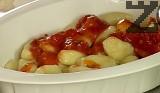 В индивидуални съдове за печене слагаме порция ньоки, поливаме с 3-4 с.л. доматен сос.
