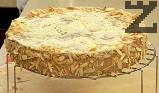 Отделяме ринга. Заглаждаме страните на тортата с помощта на шпатула. Панираме с наситнените бадемови ядки, като притискаме леко.