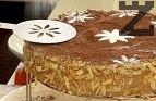 Поръсваме обилно повърхността с какао. В декоративен шаблон поръсваме пудрата захар.