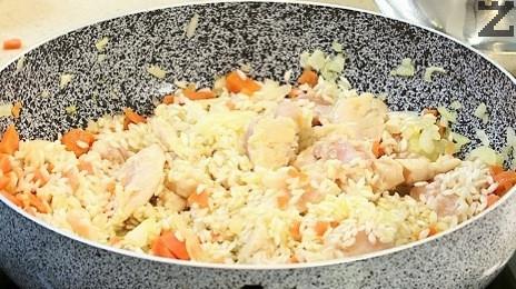 Оризът без да се мие се слага в тигана и след минута се залива с 250 мл бульон.