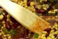 Разбъркваме и изсипваме фасула, царевицата и течността от консервата с царевица.
