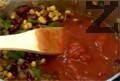 Поръсваме със захар и добавяме намачканите консервирани домати, разбъркваме.