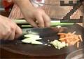 Нарязваме моркова на ивици, праза - на едро и скълцваме скилидките чесън.