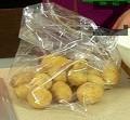 В плик за печене слагаме целите картофи, добавяме сол на вкус и зехтин. Хубаво ги разклащаме.