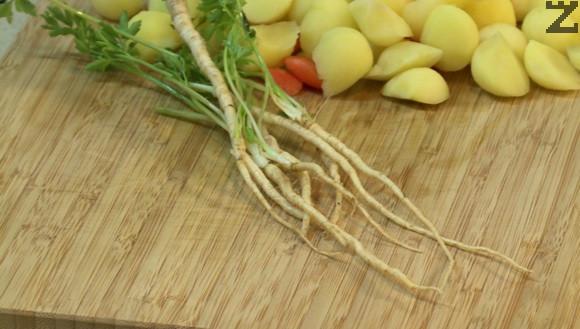 Корените на магданоза се остъргват с нож и режат на дребно. На дребно се нарязват и стъблата на магданоза. Към омекналото пиле се слагат морковите, корените и стъбла магданоз, картофите, черен пипер, дафинов лист и захар.