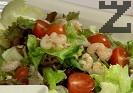 Прехвърляме салатата в чиния за сервиране. Отгоре поставяме нарязаните чери домати. Разбъркваме много добре, добавяме скаридите, поръсваме с крутони.
