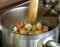Нарязваме на кубчета картофите, морковите и парчето целина. Запържваме ги леко в малко олио, като разбъркваме с дървена шпатула.