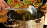 Прибавяме обеления и едро нарязан домат и наситнената чушка. Изсипваме в рибния бульон, поръсваме с 2 щипки сол и 1 щипка черен пипер.