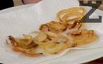 Потапяме шайбите кромид лук в брашно и ги пържим в сгорещено олио, докато придобият златист цвят. Отцеждаме лука в чиния с кухненска хартия.