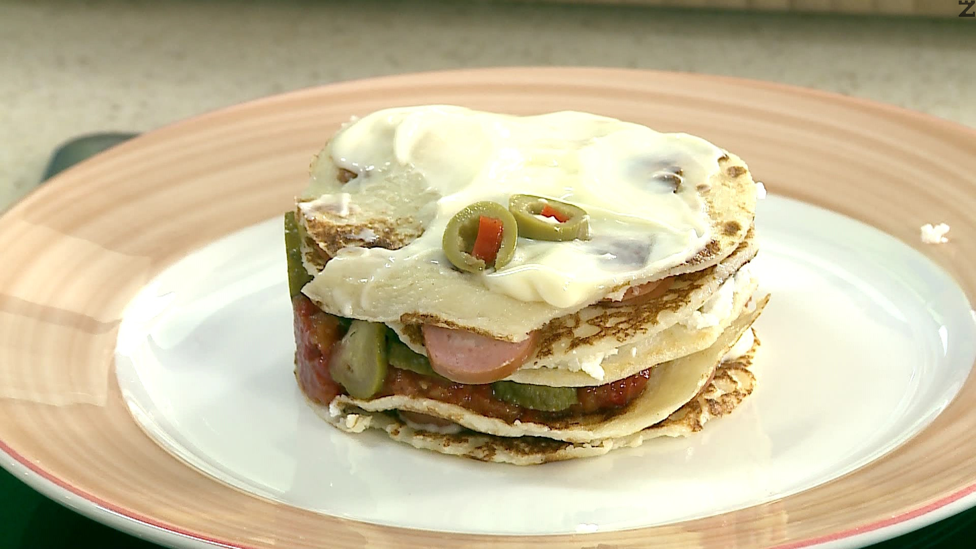 Слага се трета палачинка и покрива с настъргано сирене и четвърта палачинка.