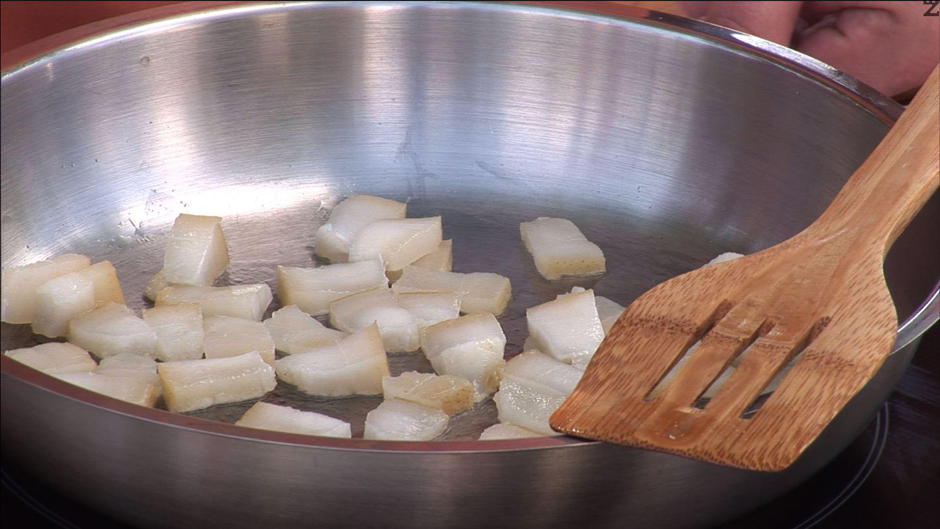 Нарязваме солената сланина на по-ситни парчета, запържваме ги в тиган.