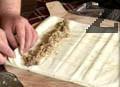 Нанасяме изстиналата смес върху 2 кори и ги завиваме на руло. Поставяме в намазнена тава.