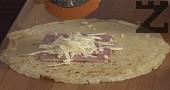 Взимаме тавичка и я намасляваме. Пълним палачинките по следния начин: в центъра на палачинката слагаме филийка шунка, отгоре настъргваме на едро сиренето и я завиваме.