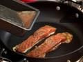 Изсипваме яйчената смес в подходящ съд и подреждаме парчетата сьомга. Запичаме филетата в загрят тиган с малко олио. Поливаме с яйчената смес и готвим под капак.