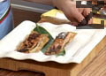 В подходяща чиния поставяме за основа лист от бананово дърво, отгоре подреждаме филетата сьомга и украсяваме с резени маринован морков и спирали краставица. Поливаме със соса и поднасяме.