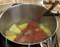 Прибавяме нарязания на едро кромид лук и след 2 минути пържене се наливат 200 мл. гореща вода. Посолява се поръсва с червен пипер и месото се задушава 20 минути под капак на тих огън. Тогава се слагат картофи нарязани на едри кубчета и ако е нужно се налива не повече от 150 мл вода. Задушаването т