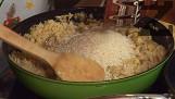 Прибавяме и ориза, запържваме за кратко. Наливаме 1 ч.ч. вода, изчакваме ориза да поеме течността, поръсваме с подправките.
