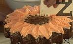Към по-голямата част добавяме оранжева сладкарска боя, размесваме с клечка за зъби. Нанасяме по повърхността на тортата, а в центъра слагаме от отделената бяла смес.