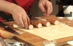 Разрязваме кренвиршите на две, разпределяме ги равномерно върху по-малкия лист тесто.