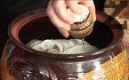 Поставяме целите скилидки чесън, наливаме олио и вино. Доливаме вода до нивото на зеленчуците. Слагаме капака, поставяме глинения съд в студена фурна. Печем на 250 градуса в продължение на 3 часа. Ако приготвяме ястието с бут, слагаме повече мазнина и печем около 4 часа.