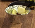 Обелваме ябълката, нарязваме я на тънки филийки. Покриваме с тях стените и дъното на еднократни формички за печене.