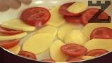 На дъното на съд за печене редим колелцата домати и картофи, посоляваме и поливаме със зехтин.