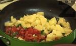 Наливаме още малко олио, запържваме за кратко пресния лук, доматите и картофите. Поръсваме с подправките.
