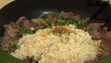 Наситняваме лука и чесъна, прехвърляме към месото, заедно с ориза.