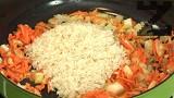 Загряваме олио, прехвърляме моркова и лука, за кратко запържваме. Прибавяме и измития ориз, заедно с нарязаните на пръчици чушки.
