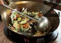 Запържваме месото и го изваждаме. Запържваме кромида, гъбите шийтаке, праза, морковите и киселите краставички. Овкусяваме със сол, захар, куркума и натриев глутамат.